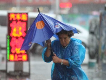 A woman walks in rainstorm in Yantai City