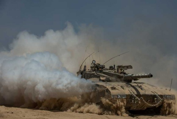 An Israeli Merkava tank runs in the field in southern Israel near the border with Gaza