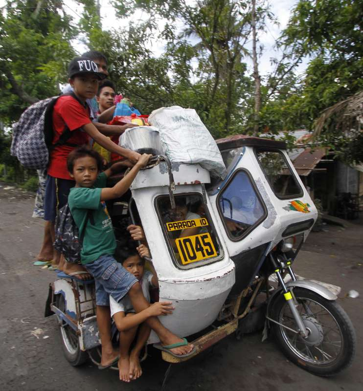 "Residents crowd on a tricycle as they evacuate from the danger zone near the Mayon Volcano in Albay Province, the Philippines, Sept. 17, 2014. The Philippine Institute of Volcanology and Seismology (PHIVOLCS) said Wednesday that Mayon Volcano in the eastern Philippine province of Albay has exhibited ""intense activity"" based on its 24-hour observation. The Philippine military said that more than 2,000 families or 10,000 individuals from five municipalities near the volcano have already been transferred to various evacuation centers."
