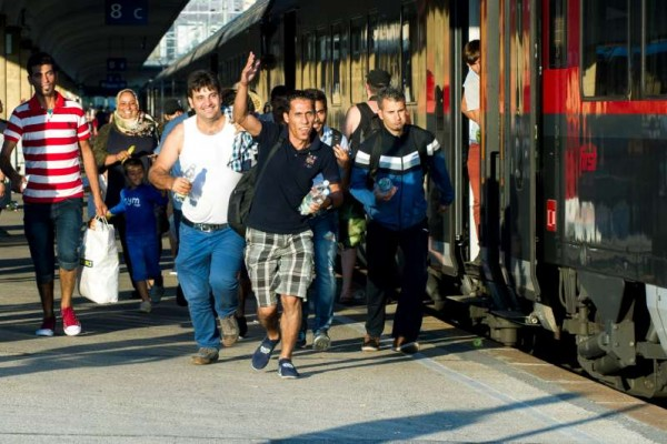 HERE WE COME: Refugees run to board a train leaving for Munich, Germany, at the Westbahnhof Railway Station in Vienna, Austria