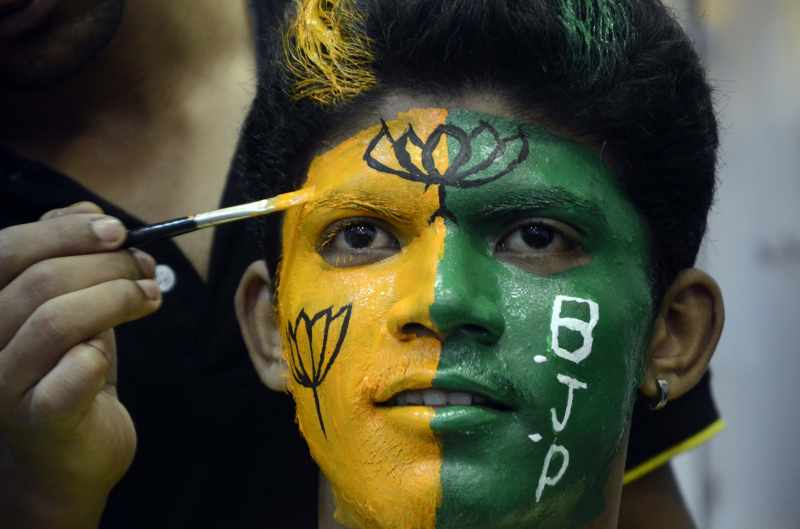 A BJP supporter gets his face coloured in party's colours in Mumbai