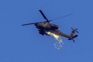 An Israeli Apache helicopter launches flares in the air over southern Israel near the border with Gaza, on the 11th day of Operation Protective Edge, on July 18, 2014. Israeli Prime Minister Benjamin Netanyahu said on Friday that the Israel Defense Forces (IDF) is ready to expand the ground operation in the Gaza Strip if needed.