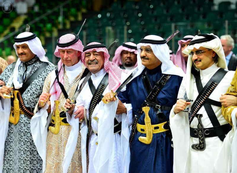 Saudi Arabia's second deputy Prime Minister Muqrin bin Abdulaziz (3rd L) and visiting Britain's Prince Charles (2nd L) perform traditional Saudi dance known as `Arda` during Janadriya Culture Festival in Riyadh on Feb.18, 2014. (Photo: Xinhua/IANS)