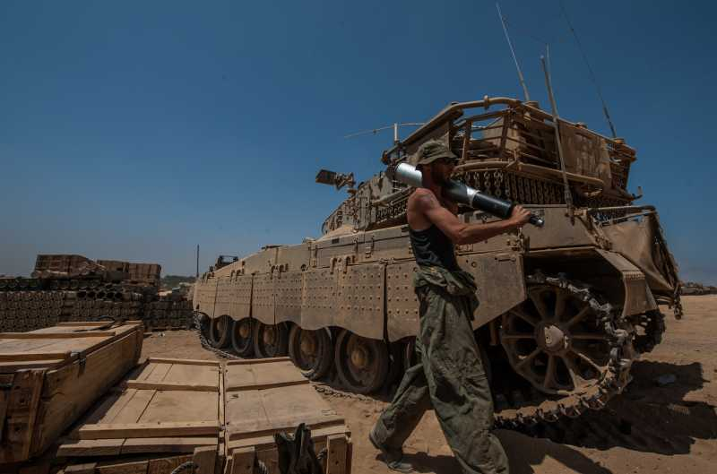 GAZA BORDER, July 31, 2014 (Xinhua) -- An Israeli soldier carries a shell at an army deployment area in southern Israel near the border with Gaza. Three Israeli soldiers were killed in the Gaza Strip on Wednesday, the Israel Defense Forces (IDF) spokesperson unit said in a statement.