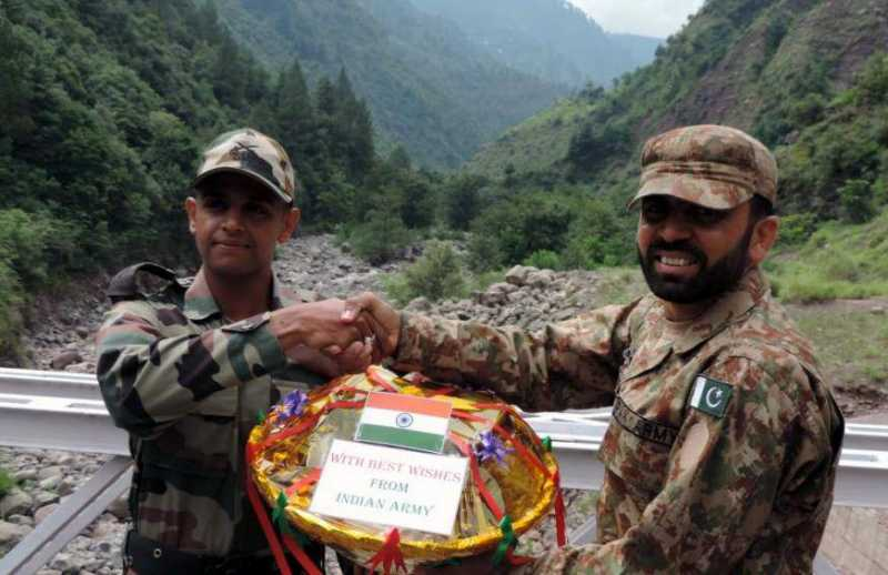 """Indian and Pakistani troops deployed at Kaman Aman Setu and Tithwal celebrated Eid-ul-Fitr by exchanging sweets. In a brief ceremony, organized at Kaman Aman Setu at Uri and Tithwal at Tangdhar Jammu and Kashmir""""s of Kupwara District, both Indian and Pakistani Armed Forces deployed on line of control greeted each other on the occasion of Eid-ul-Fitr and also exchanged sweets and pleasantries on July 29, 2014. (Photo: IANS)"""