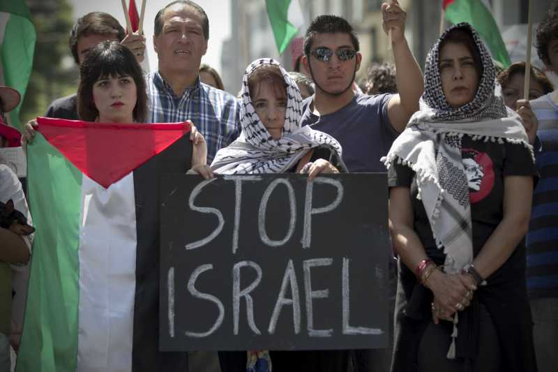 A woman holds a placard during a protest against Israeli's airstrikes on Gaza and in solidarity with the Palestinians, in Mexico City, capital
