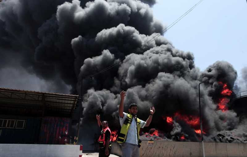 Palestinian firefighters react as flames engulf the fuel tanks of the main power plant which supplies electricity to the Gaza Strip, in Gaza City
