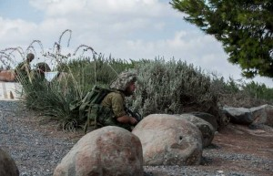Israeli soldiers take position during an operation at an outpost in southern Israel near the border with Gaza