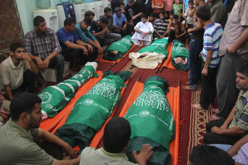 GAZA:  Palestinian Mourners gather around the bodies of six members of al-Hashash family, who were killed in an Israeli air strike on their home