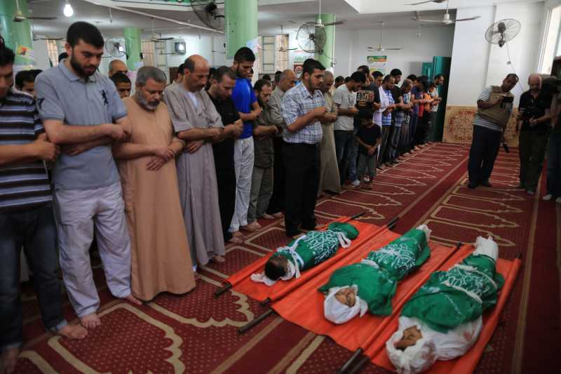 People pray over the bodies of three siblings of the Abu Musallam family, who were killed in an Israeli tank attack, during their funeral in northern Gaza strip town of Beit Lahia