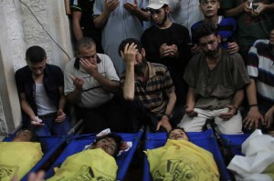 Palestinians gather around the bodies of the boys of Baker family, at a mosque before their funeral in Gaza City, on July 16, 2014. A new Israeli war jets airstrike on western Gaza city killed on Wednesday four Palestinian children and wounded ten others while they were on the beach of Gaza, medics and witnesses said.