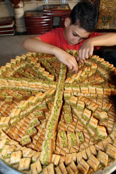 DAMASCUS: A Syrian boy prepares Arabic desserts in the al-Midan neighborhood in Damascus