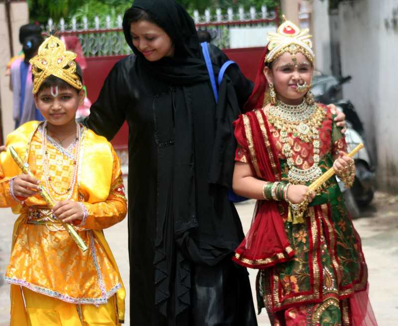 A Muslim woman with her kids dressed as Lord Krishna and Radha returning home after a school competition on the eve of Janmastami in Varanasi, the constituency of Prime Minister Modi