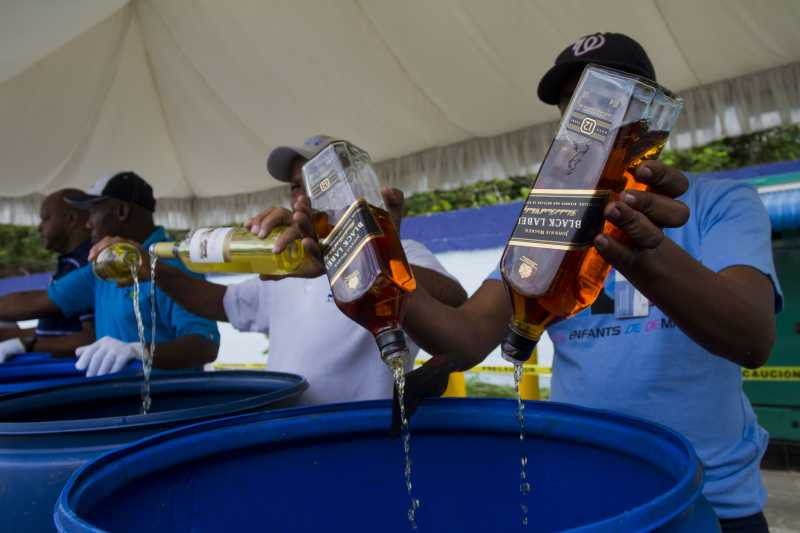 ANTO DOMINGO:  Employees of the Customs General Direction (DGA, for its acronym in Spanish), pour alcoholic beverages after being seized, in Santo Domingo, Dominican Republic. The DGA destroyed on Thursday 2000 boxes of whisky and alcoholic beverages, seized when being entered by contraband on national territory. The 2000 boxes, equivalent to 16,723.13 liters of different types of alcoholic beverages, with an approximate value of 11,793,331.76 dominican pesos, informed the engineer Fernando Fernandez, head of the DGA.