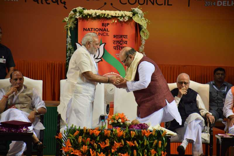 Prime Minister Narendra Modi congratulating newly appointed BJP President Amit Shah at the BJP National Council meeting in New Delhi on Aug. 9, 2014. (Photo: IANS)