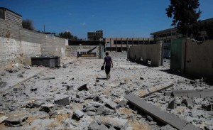 A Palestinian inspects the damage at Ali ibn Abi Taleb government school that was targeted overnight by Israeli airstrikes in Gaza City, on August 26, 2014. A ceasefire came into effect on Tuesday at 7:00 a.m. (0400 GMT), after an agreement, brokered by Egypt, reached between Israel and the Palestinian factions, including Hamas movement.  FILE PHOTO
