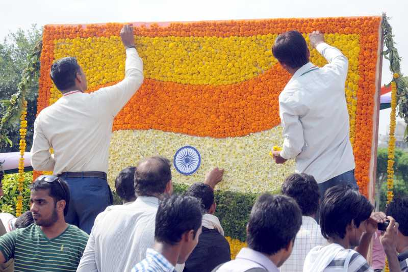 NDMC workers busy making Indian flag using flowers on the eve of 68th Independence Day in New Delhi on Aug 14, 2014. (Photo: IANS)