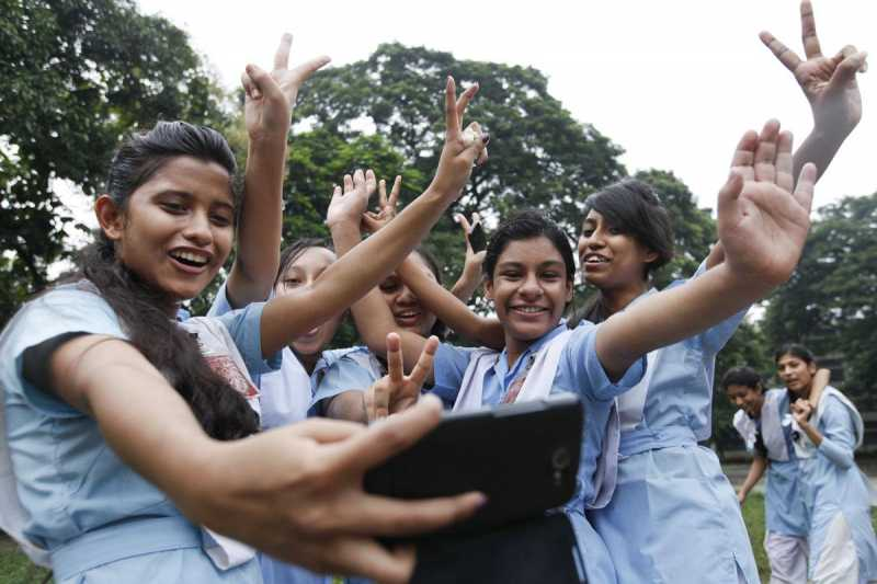 Students celebrate after declaration of Higher Secondary results in Dhaka, Bangladesh on Aug 13, 2014. (Photo: bdnews24/IANS)