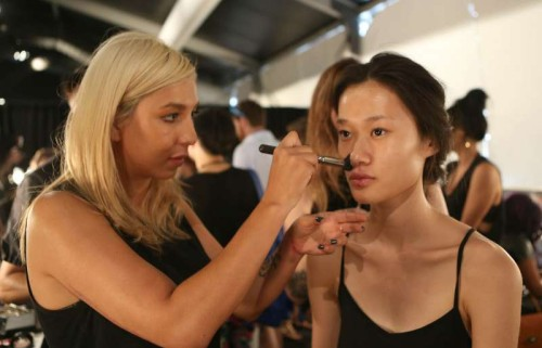 Chinese model Zhang Huijun (R) has make-up applied backstage during the 2015 New York Fashion Week in New York, the United States