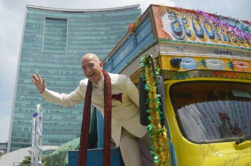 Jeff Bezos, Founder and CEO, Amazon.com with Amit Agarwal, Vice President and Country manager, Amazon.in atop a truck in Bangalore on Sept. 28, 2014. (Photo: IANS)