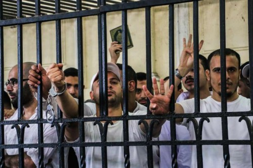 (140519) -- CAIRO, May 19, 2014 (Xinhua) -- Egyptian defendants react in a cage on a court of their trial over violence during 2013 Alexandria clashes in Sidi Gaber neighborhood, in Alexandria, coastal city of Egypt, on May 19, 2014. An Egyptian court sentenced on Monday an Islamic supporter of ousted president Mohamed Morsi to death, 18 others to life imprisonment and 10 over violence and murder charges in reaction to Morsi's removal last year, official MENA news agency reported. (Xinhua/Asmaa Abdelatif)(cy)