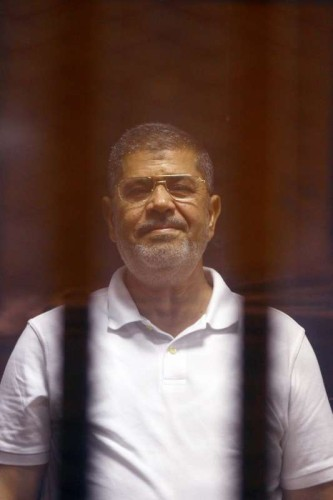 The deposed Islamist president Mohamed Morsi is seen inside a glass defendants cage during his trial in Cairo