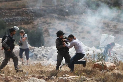 An Israeli soldier clashes with a Palestinian youth during a protest in the West Bank village of Wadi Fukin near city of Bethlehem on Sept. 5, 2014. On Sunday, Israel announced the appropriation of 1,000 acres of Palestinian land in the Bethlehem area in the occupied West Bank.