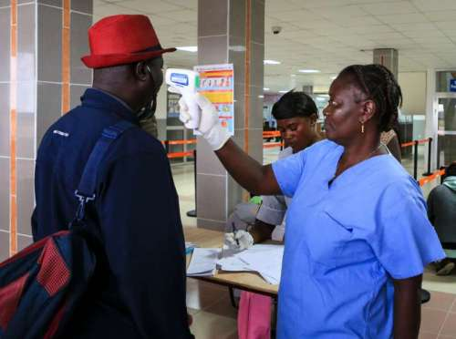 An airport worker measures body temperature for passengers at the Lungi International Airport in Freetown, capital of Sierra Leone.