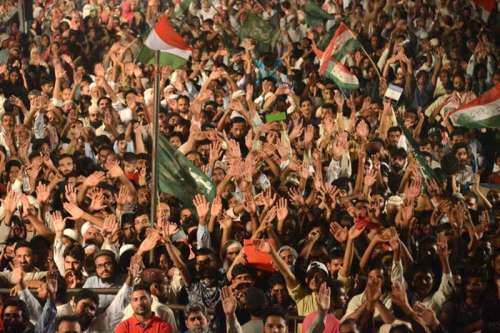 Supporters of religious leader Tahir-ul-Qadri raise up hands during an anti-government protest