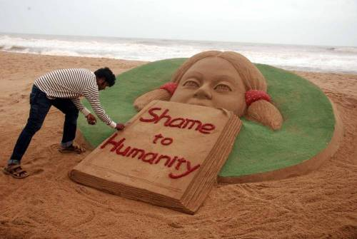 Renowned sand artist Sudarsan Pattnaik condemns rape of a 6-year-old in Bangalore through his art on Puri beach in Odisha on July 22, 2014. (Photo: IANS)