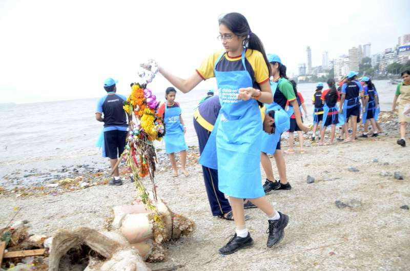 School students engaged in cleaning of the Girgaon Chaupati, a day after Ganapati immersions in Mumbai on Sept 9, 2014. (Photo: Sandeep Mahankal/IANS)
