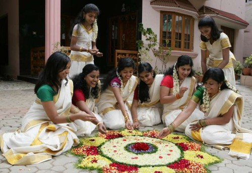 Women decorating Rangoli with flowers, on the eve of Onam Festival, in Bangalore
