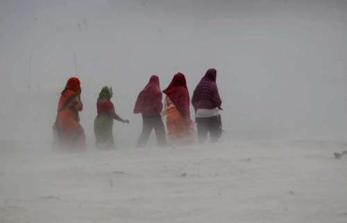 People walk on the banks or river Ganga during a storm in Allahabad, on Oct.13, 2014. (Photo: IANS)