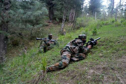 Soldiers take position during an encounter in Waderbala forests of Handwara, Jammu and Kashmir.
