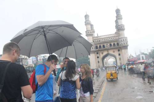 Foreign tourists enjoy themselves during rains at Charminar in Hyderabad