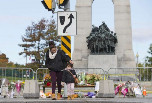 People pay their respect to fallen solider at the National War Memorial in Ottawa, Canada, Oct. 23, 2014. Canadian soldier Nathan Cirillo was fatally shot by a gunman at the National War Memorial one day ago. (Xinhua/Zou Zheng)