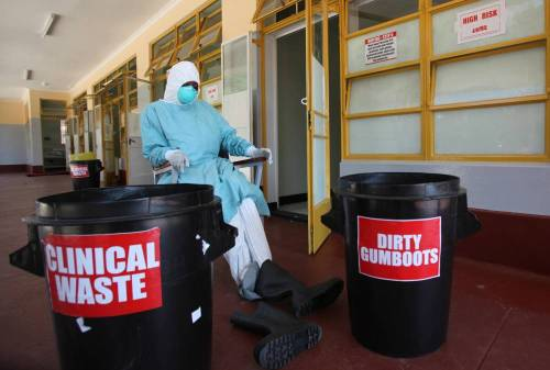 A nurse works inside one of the rooms created for Ebola quarantine center during a media tour at Wilkins Infectious Disease Hospital in Harare, Zimbabwe.