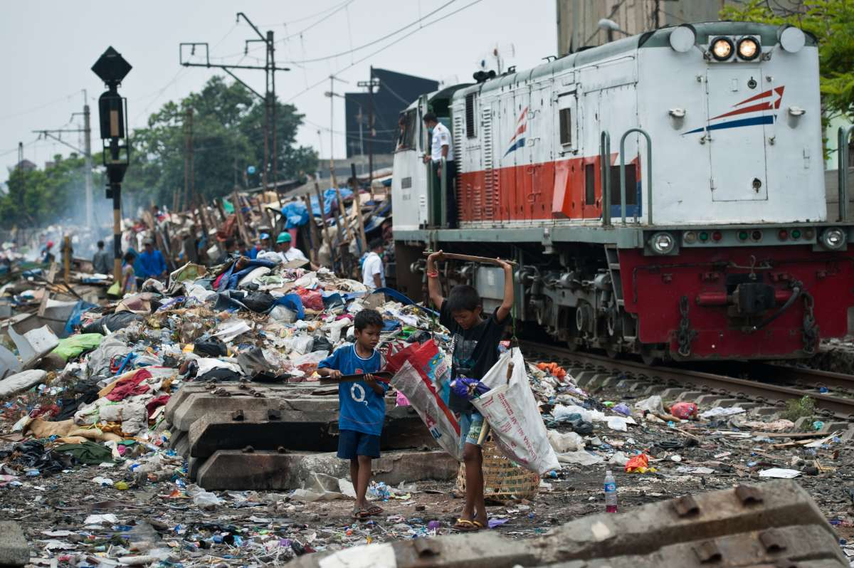 Children collect the demolition on the edge of the railway in Jakarta, Indonesia, Oct. 14, 2014. The Government of Jakarta curbs illegal housings along railway lines, which can endanger the safety of train travel.