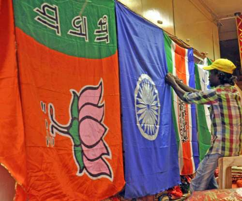A worker arranges flags of different political parties in Mumbai.