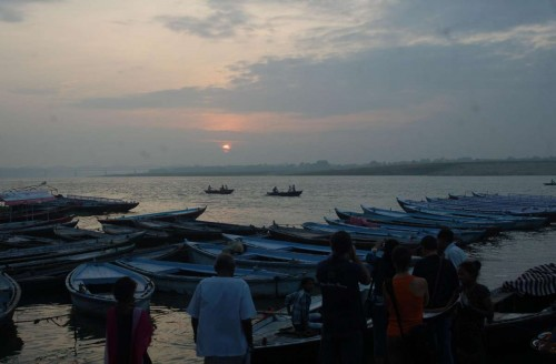 Foreigners click pictures of sunrise on the banks of Ganga river in Varanasi.
