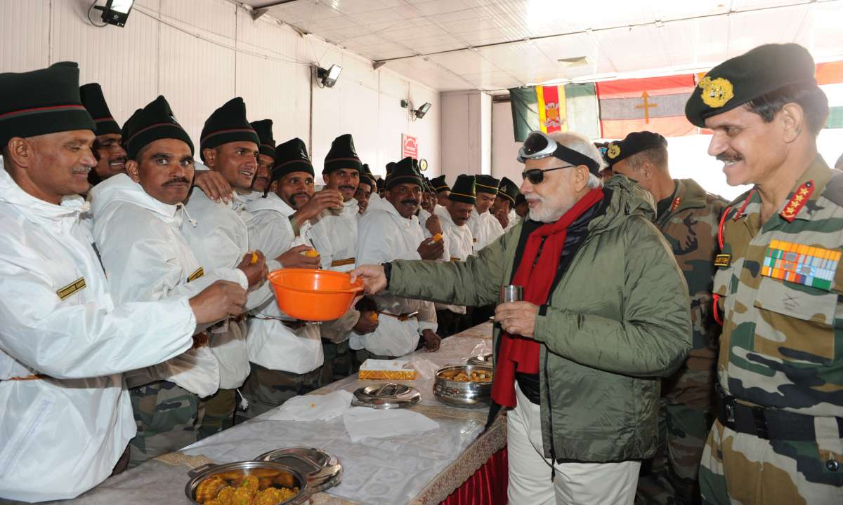 The Prime Minister, Shri Narendra Modi sharing sweets with Indian Army Jawans on the occasion of Diwali, at Siachen Base Camp on October 23, 2014. The Chief of Army Staff, General Dalbir Singh is also seen.