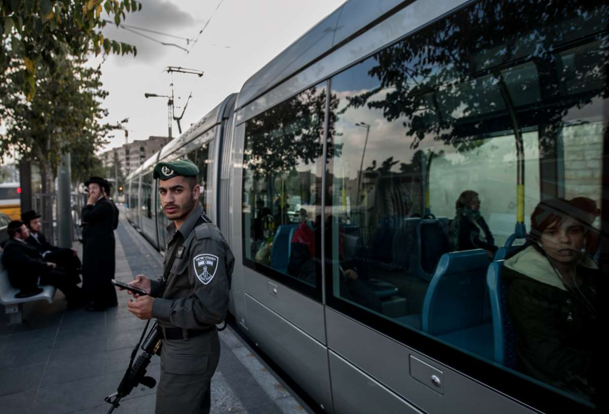 An Israeli border policeman stands guard at Shimon Hatzadik light rail station where an attack occurred in East Jerusalem, on Nov. 5, 2014. A Palestinian motorist rammed his van into pedestrians and then assaulted them with a metal bar in tension-ridden Jerusalem Wednesday, leaving one person dead and 13 others injured, before being shot dead by Israeli police.