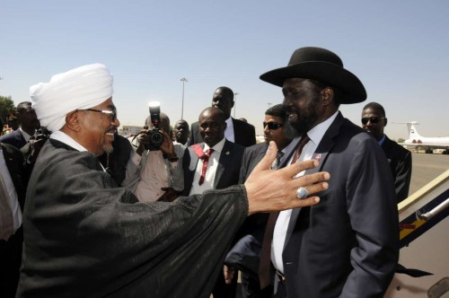 Sudanese President Omar al-Bashir greets South Sudan's President Salva Kiir at Khartoum's airport, Sudan, on Nov. 4, 2014. Sudan and South Sudan on Tuesday vowed to peacefully settle the outstanding issues, namely the security ones so that they would live side by side in peace and stability.