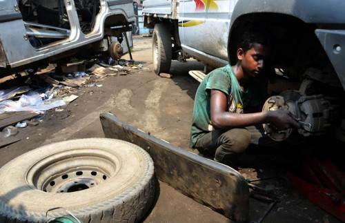 A boy works on a car at a vehicle repair garage