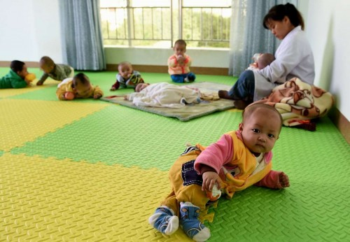 Rescued trafficked babies play at the Kaiyuan Children's Welfare Center in Kaiyuan City, southwest China's Yunnan Province, Nov. 11, 2014. Police in Yunnan have rescued 11 babies from a trafficking ring and are trying to find their parents. The babies, who are all in good health, are now looked after at the Kaiyuan Children's Welfare Center.