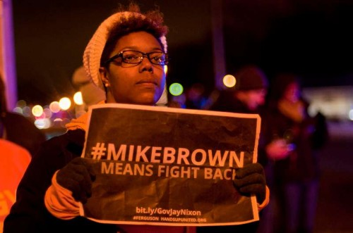 A woman takes part in a protest against the grand jury's decision not to charge police officer Darren Wilson in the fatal shooting of African American youth Michael Brown, in Ferguson, Missouri, the United States, Nov. 24, 2014. Violence erupted Monday night in Ferguson after the announcement that police officer Darren Wilson would not be indicted for shooting unarmed 18-year-old Michael Brown