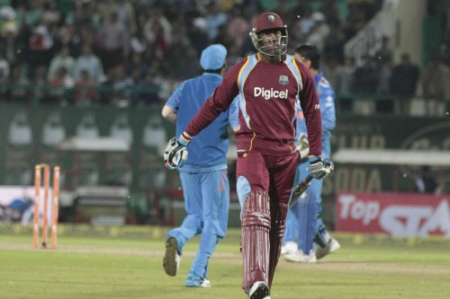 Dharmasala: West Indian players Andre Russell walks back to the pavilion after getting dismissed during the fourth ODI match between India and West Indies at Himachal Pradesh Cricket Association Stadium, Dharmasala on Oct.17, 2014.
