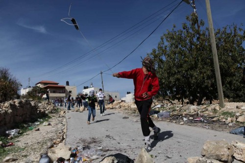 A Palestinian protester hurls stones toward Israeli soldiers during clashes in Jerusalem