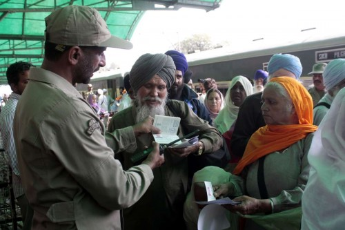 A Pakistani ranger official checks passports of Indian Sikh pilgrims as they arrive at a railway station in eastern Pakistan's Lahore on Nov. 4, 2014. Thousands of Sikh pilgrims arrived in Lahore to celebrate the 545th birth anniversary of Sri Guru Nanak Dev which falls on Nov. 6.