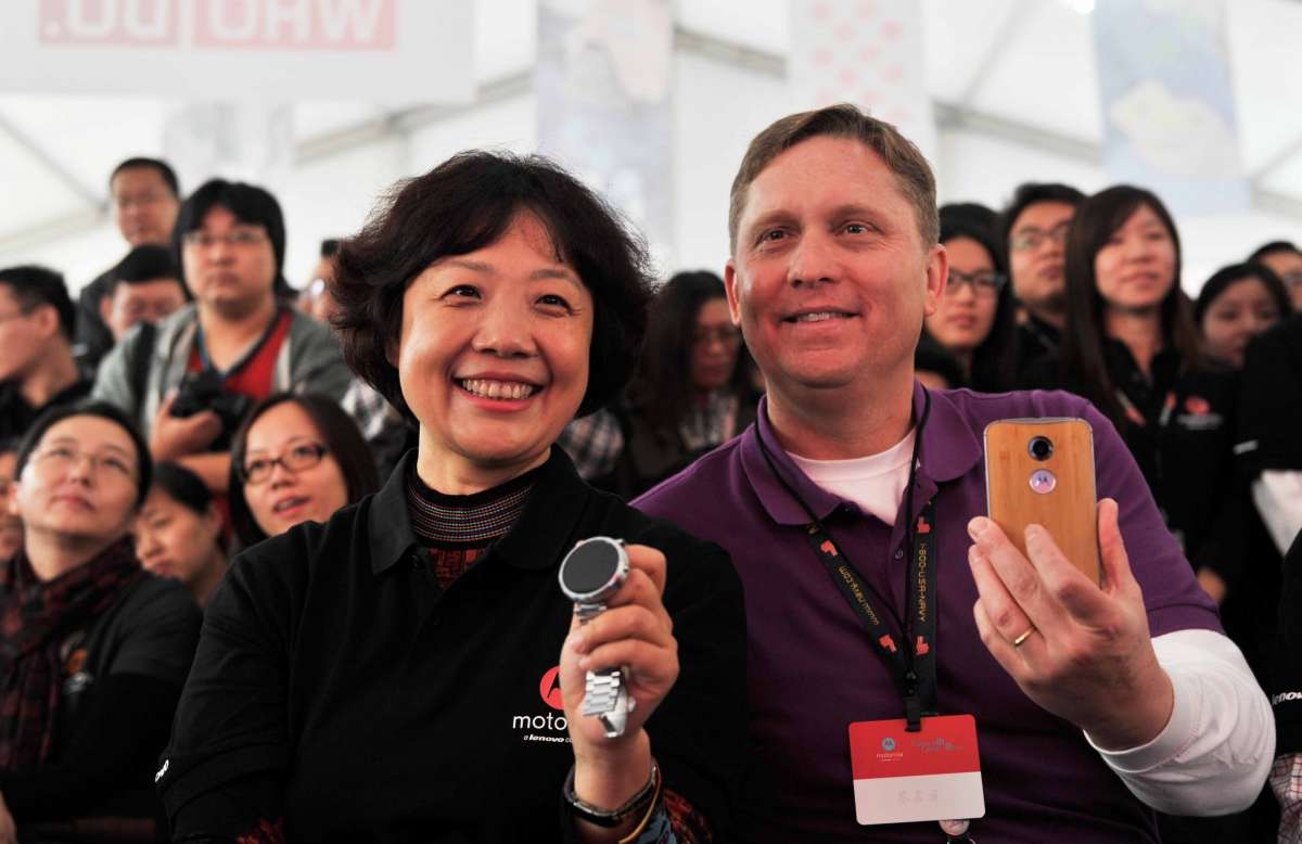 Gregg Locher (R), director of Business Operation at Motorola Mobility, and Lenovo Group's Senior Vice President Qiao Jian show products while attending a celebration in Beijing, China